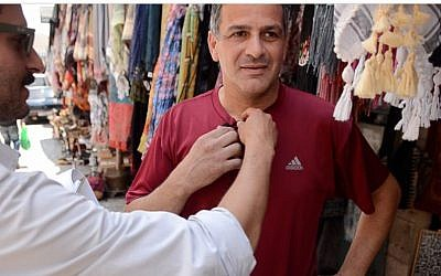Joseph Shamash, left, prepares a merchant in Bethlehem for his interview (photo credit: courtesy)