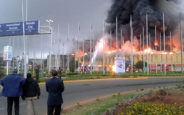 Onlookers watch as black smoke billows from the international arrivals hall of Jomo Kenyatta International Airport in Nairobi, Kenya, on Wednesday, August 7. (photo credit: AP/Segeni Ngethe)