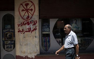 """An Egyptian man walks in front of a pharmacy marked with anti-Coptic and anti-coup graffiti in Assiut, Upper Egypt, Tuesday, Aug. 6, 2013. Arabic grafitti reads, """"No to the coup and yes to legitimacy."""" (Photo credit: AP/Manu Brabo)"""