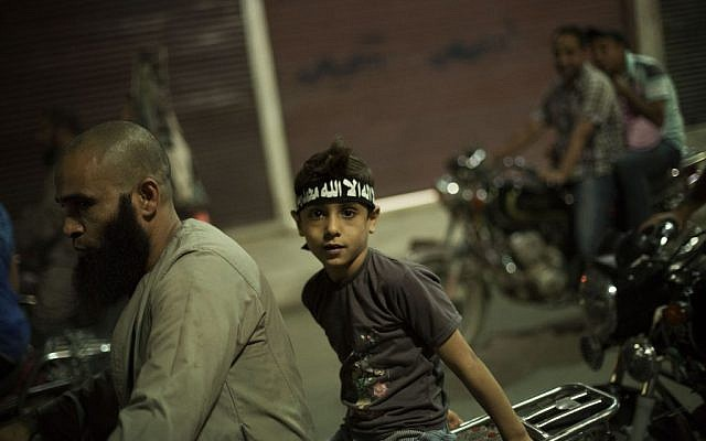 An Egyptian Muslim child rides on the back of a motorbike during a rally supporting former President Mohammed Morsi in Assiut, Upper Egypt, Tuesday, Aug. 6, 2013 (photo credit: AP/Manu Brabo)