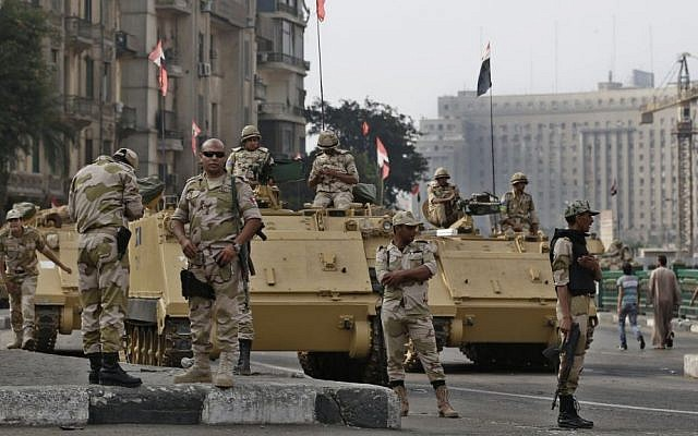 Egyptian soldiers take their positions on top and next to their armored vehicles while guarding an entrance of Tahrir Square, in Cairo, Egypt, Friday, August 16 (photo credit: AP/Hassan Ammar)