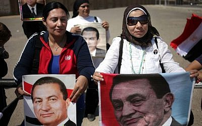 Supporters of former Egyptian President Hosni Mubarak hold posters of him as they protest outside the Cairo Police Academy-turned-court in Cairo, Egypt, Sunday, Aug. 25, 2013 (AP/Khalil Hamra)