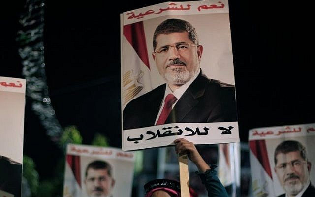 Supporters of Egypt's ousted president Mohammed Morsi hold his posters with Arabic writing which reads 'Yes for legality, No for the coup' during a protest outside Rabaah al-Adawiya mosque on Tuesday. (photo credit: AP/Khalil Hamra)