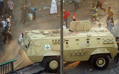 Supporters of ousted Islamist President Mohammed Morsi capture an Egyptian security forces vehicle at the Ministry of Finance in Cairo, Egypt, Wednesday, August 14, 2013. (photo credit: AP Photo/Mohsen Nabil)