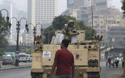 An Egyptian walks in front of an army armored vehicle guarding an entrance of Tahrir Square, in Cairo, Egypt, on Friday, August 16, 2013. (photo credit: AP/Hassan Ammar)