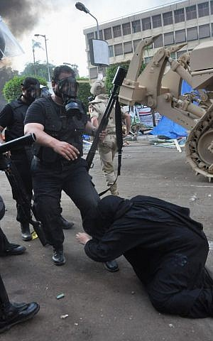 An Egyptian security force confronts a woman at a sit-in camp set up by supporters of ousted Islamist President Mohammed Morsi near Cairo University in Cairo's Giza district, Egypt, Wednesday, August 14, 2013. (photo credit: AP Photo/Hussein Tallal)