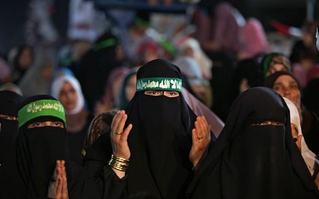 """Supporters of Egypt's ousted President Mohammed Morsi wear headbands with Arabic writing reading """" No god but Allah and Mohammed is the prophet"""" as they pray outside Rabaah al-Adawiya mosque, where protesters have installed a camp and hold daily rallies at Nasr City in Cairo, Egypt on Sunday. (photo credit: AP/Khalil Hamra)"""