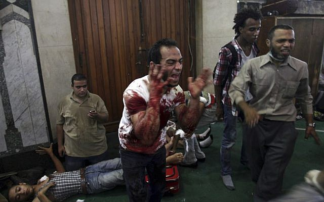 An Egyptian man covered with blood shouts inside the Al-Fath mosque that is being used as a makeshift hospital and is receiving casualties from clashes between security forces and supporters of Egypt's ousted President Mohammed Morsi in Ramses Square, downtown Cairo, Egypt, Friday, Aug. 16 (photo credit: AP)