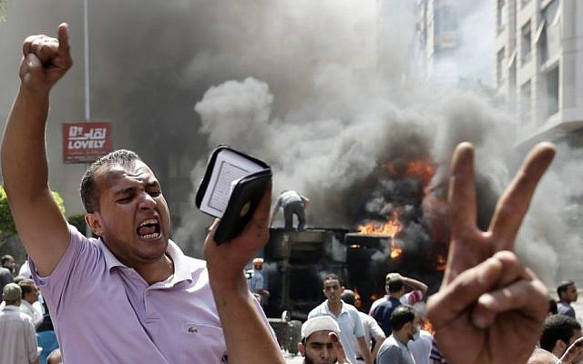 Supporters of Egypt's ousted president Mohammed Morsi chant slogans against Defense Minister Gen. Abdel-Fattah el-Sissi during clashes with Egyptian security forces in Cairo, Egypt, on Wednesday (photo credit: AP/Hassan Ammar)