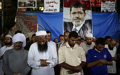 Supporters of Egypt's ousted President Mohammed Morsi pray outside Rabaah al-Adawiya mosque, where supporters of Egypt's ousted President Mohammed Morsi have installed a camp and hold daily rallies at Nasr City, in Cairo, Egypt, late Tuesday, July 30, 2013 (photo credit: AP/Hassan Ammar)