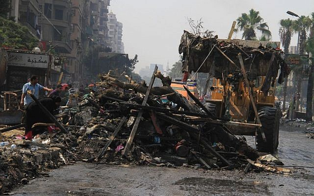Soldiers clear debris as people sift through it the day after Egyptian security forces clear two encampments of supporters of ousted President Mohammed Morsi in Cairo's Nasr City on Thursday. (photo credit: AP/Ahmed Gomaa)