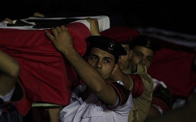 Egyptian military and policemen carry coffins, covered with national flags, containing the bodies of off-duty policemen who were killed near the border town of Rafah, North Sinai, upon their arrival at Almaza military airport, Cairo, Egypt, Monday, Aug. 19, 2013 (photo credit: AP/Khalil Hamra)