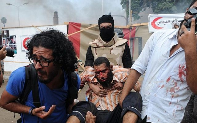 Supporters of ousted Islamist president Mohammed Morsi carry an injured protester at a sit-in camp in Cairo, August 14, 2013. (photo credit: AP/Mohammed Asad)