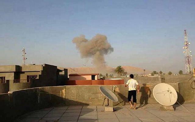 Smoke rises after a bomb attack in Tuz Khormato, 130 miles (210 kilometers) north of Baghdad, Iraq, Saturday, Aug. 10, 2013 (photo credit: AP)