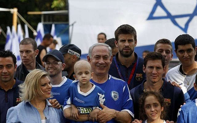 Prime Minister Benjamin Netanyahu, center, and his wife Sara, second left, pose for a picture with FC Barcelona players Xavi, far left, Gerard Pique, center right, and Lionel Messi, next to Pique, during a football event with young Israeli cancer patients near Tel Aviv, Israel, Sunday, Aug. 4, 2013 (photo credit: AP/Gali Tibbon, Pool)