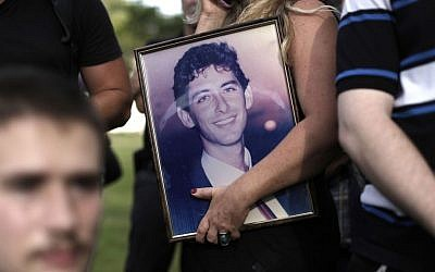 An Israeli holds a portrait of a relative killed in a terror attack during a protest in Tel Aviv on Monday as people protested the government's decision to release 26 Palestinian prisoners, most of them held for deadly attacks, as part of a US-brokered deal that led to a resumption of Mideast negotiations. (photo credit: AP Photo/Tsafrir Abayov)