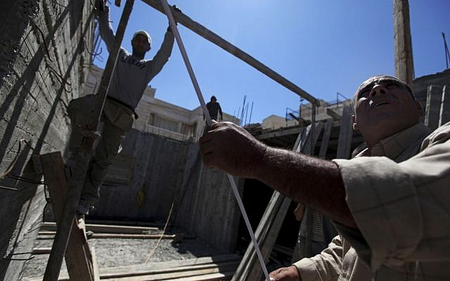 Palestinian men work at a construction site in the East Jerusalem neighborhood of Ramat Shlomo, May 4, 2010. (photo credit: AP/Tara Todras-Whitehill)