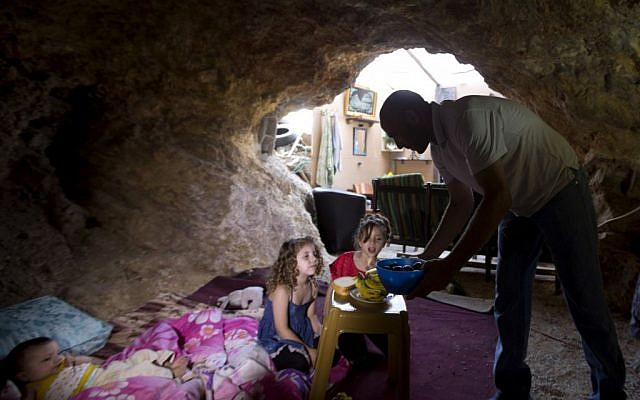 Palestinian Khaled Zir sits with his children inside a cave in the east Jerusalem neighborhood of Silwan, Tuesday, Aug. 27, 2013. Zir said the family moved into a cave after their home was demolished by Israeli authorities. (photo credit: AP/Sebastian Scheiner)