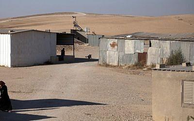 A Bedouin woman walks through the village of al-Sira, Israel, on Wednesday. (photo credit: AP/Sebastian Scheiner)