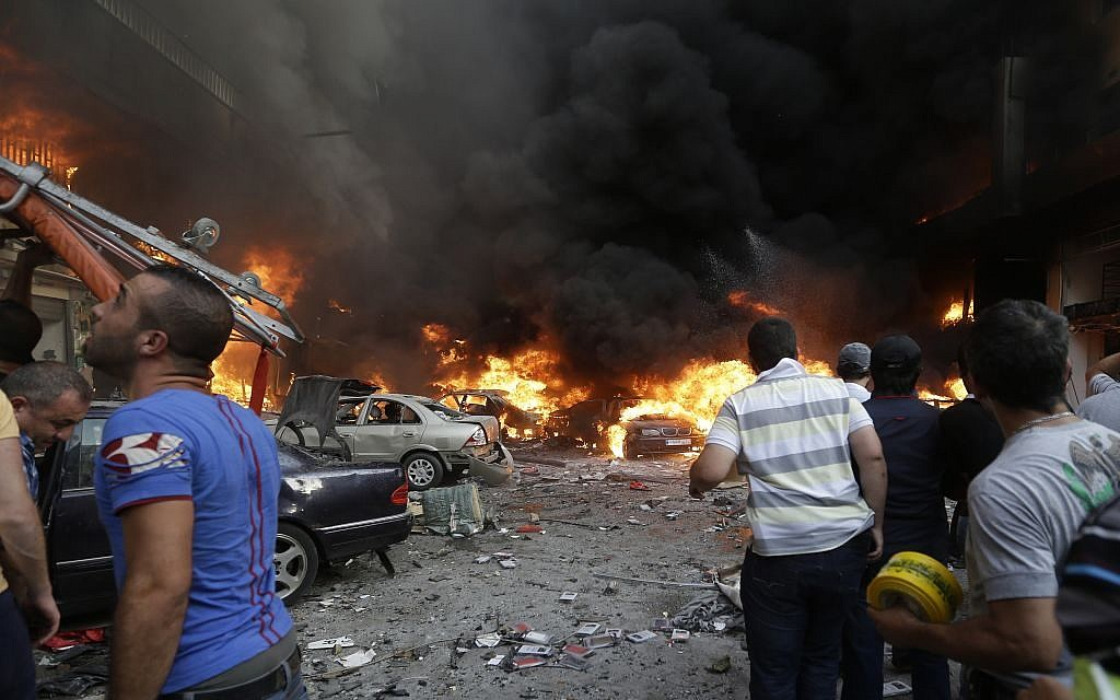 Lebanese citizens gather at the site of a car bomb explosion in southern Beirut, Lebanon, Thursday, Aug. 15, 2013. (Photo credit: AP /Hussein Malla)