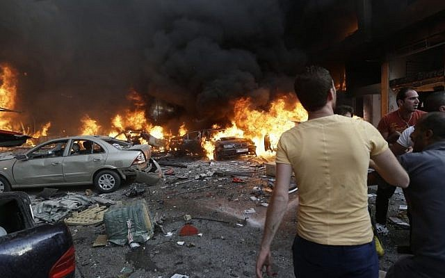 Lebanese citizens gather at the site of a car bomb explosion in southern Beirut, Lebanon, Thursday, Aug. 15, 2013. (Photo credit: AP/Hussein Malla)