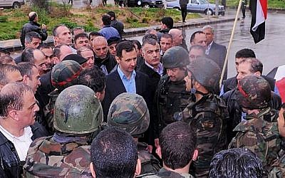 Undated photo posted on Syrian President Bashar Assad's official Instagram account showing Assad visiting with soldiers in Baba Armr, Homs province. (photo credit: AP/Syrian Presidency via Instagram)