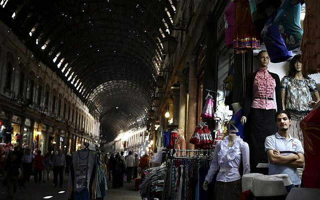 A Syrian shopkeeper waits for customers at the popular Hamidiyeh old market, in Damascus, Thursday, August 22, 2013. (photo credit: AP/Hassan Ammar)