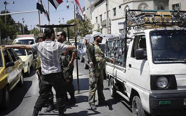 Syrian military soldiers check identifications and search vehicles at a check point on Baghdad street, in Damascus, on Wednesday, August 21, 2013. (photo credit: AP/Hassan Ammar)