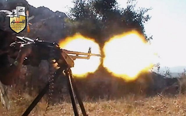 A rebel fighter fires a gun in a valley in an unidentified location in Latakia province, Syria, Sunday, Aug. 11, 2013.  (photo credit: AP/Sham News Network via AP video)