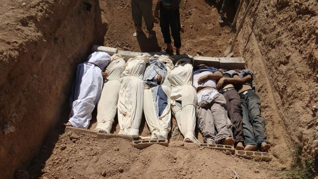 Bodies being buried after last month's chemical attack near Damascus (photo credit: AP/Shaam News Network)