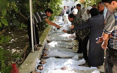 Syrian citizens try to identify dead bodies after an alleged poisonous gas attack near Damascus, on August 21, 2013 (photo credit: AP/Local Committee of Arbeen)