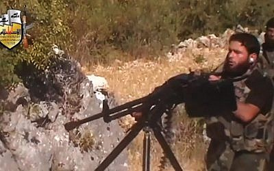 A rebel fighter fires a gun in a valley in an unidentified location in Latakia province, Syria, August 11, 2013 (photo credit: AP)