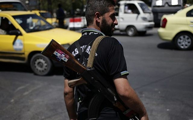 A Syrian soldier holds an AK-47 with a sticker of Syrian President Bashar Assad and Arabic that reads 'Syria is fine,' as he stands guard at a check point on Baghdad street, in Damascus, Wednesday, August 21, 2013. (photo credit: AP/Hassan Ammar)