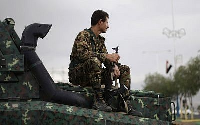 Illustrative photo of a Yemeni policeman sitting on an armored near the US Embassy in Sanaa, Yemen,  in August 2013 (photo credit: AP/Hani Mohammed)