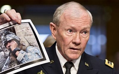 Gen. Martin Dempsey, chairman of the Joint Chiefs of Staff, holds up a photo of a deployed American soldier as he testifies before the Senate Armed Services Committee at his reappointment hearing, on Capitol Hill in Washington. July 18, 2013. (photo credit: AP/J. Scott Applewhite)