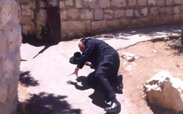 Avrohom Mondrowitz, indicted for child rape in NY, climbs to his feet after being shoved to the ground by an unknown assailant in Jerusalem. (photo credit: Youtube/ screengrab)