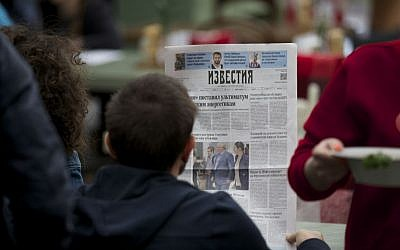 "A street cafe visitor reads a fresh Russian newspaper ""Izvestia"" with a front page pictures of Russian lawyer Anatoly Kucherena, center, and National Security Agency leaker Edward Snowden, center left, taken on Thursday, Aug. 1, 2013 at Sheremetyevo airport outside Moscow, Russia. (AP Photo/Alexander Zemlianichenko)"