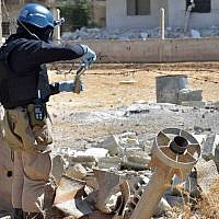 A member of a UN chemical weapons investigation team takes samples from sand near Damascus, Syria, August 28, 2013. (AP/United Media Office of Arbeen)