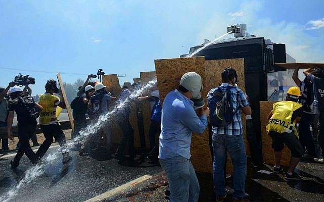 People try to protect themselves as riot and paramilitary police officers fire tear gas and use water cannons to disperse protesters outside the Silivri jail complex in Silivri, Turkey, Monday, Aug. 5, 2013 (photo credit: AP)