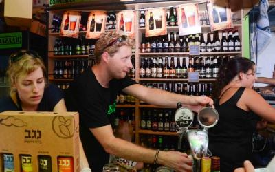 Yuval Reznikovich pouring a beer at his craft beer kiosk in Tel Aviv's Carmel Market. (photo credit: Courtesy Beer Bazaar)