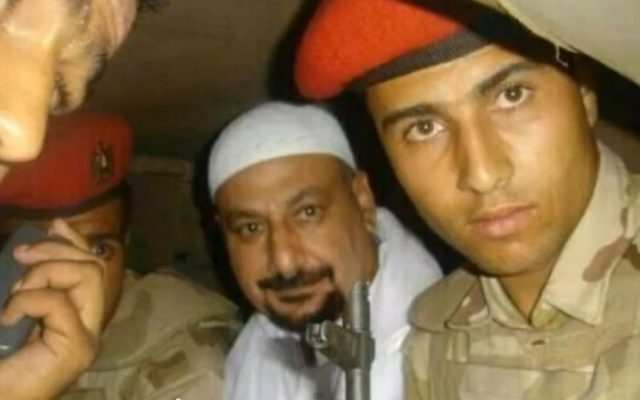Safwat Hegazy, in white, with soldiers after being captured, in a photo which aired on Egyptian State TV. (Screenshot: YouTube)