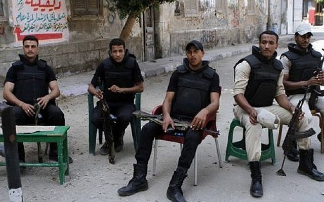 Egyptian security forces taking a break in Beni Sueif, south of Cairo, Egypt, on Friday (photo credit: AP/Sabry Khaled/El-Shorouk)
