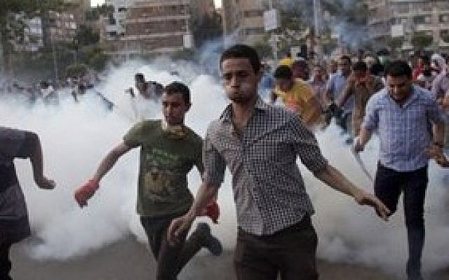 Supporters of Egypt's ousted president Mohammed Morsi run for cover from tear gas fired by police (not seen), during a protest in Cairo, Egypt, on August 30, 2013 (photo credit: AP/Khalil Hamra)