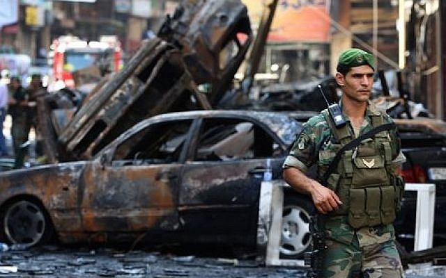 A Lebanese soldier passes in front of burned cars at the site of a car bombing in southern Beirut, on August 16, 2013 (photo credit: AP/Hussein Malla/File)