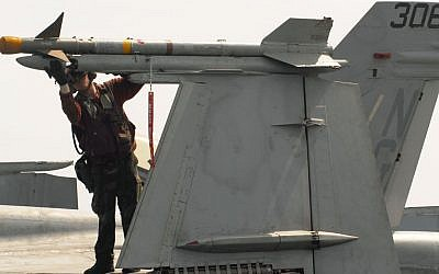A Navy officer checking an AIM-9 Sidewinder missile for proper mounting on an F/A-18C Hornet aircraft, prior to flight operations aboard the aircraft carrier USS John C. Stennis in 2007. (photo credit: Seaman Josue Leopoldo Escobosa/ US Navy/Department of Defense).