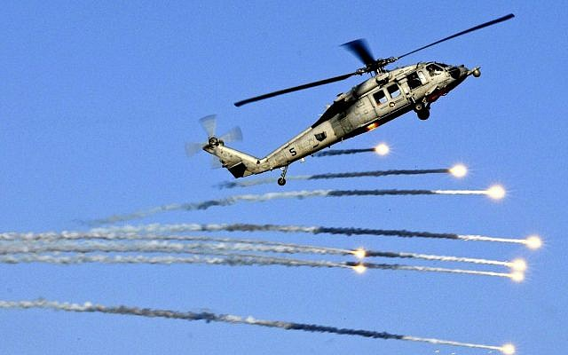 A US MH-60S Seahawk helicopter launches flares during a drill in the skies above the aircraft carrier USS Abraham Lincoln in the Mediterranean Sea on July 25, 2012. (photo credit: Seaman Joshua E. Walters/ US Navy, Department of Defense)