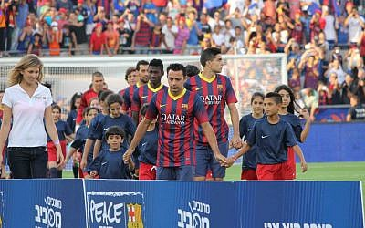 Xavi, center in jersey, escorting children onto the pitch for the pre-ceremony events. (photo credit: Yehuda Kirschenbaum)