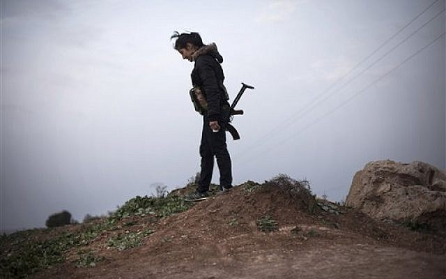 A Kurdish female member of the Popular Protection Units stands guard at a checkpoint near the northeastern city of Qamishli, Syria, March 3, 2013. (photo credit: AP/Manu Brabo)