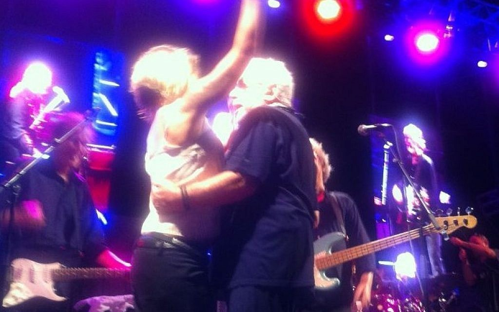 Eric Burdon dances with an enthusiastic fan who climbed up on stage early in his show at the Zappa Shuni Amphitheater in Binyamina on Thursday night. (photo credit: ToI staff)