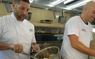Assaf Granit (left) and Tomer Ballas of Lechem shel Tomer, serving up chickpeas and meat patties on day 17 of the FoodTrip (photo credit: Jessica Steinberg/Times of Israel)